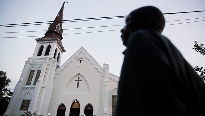 The steeple of Emanuel African Methodist Episcopal Church stands as a pedestrian passes early Sunday, June 21, 2015, in Charleston, S.C.