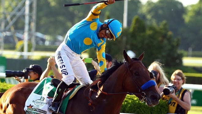 Victor Espinoza, celebrates atop American Pharoah after winning the 147th running of the Belmont Stakes Saturday to become the 12th Triple Crown winner.