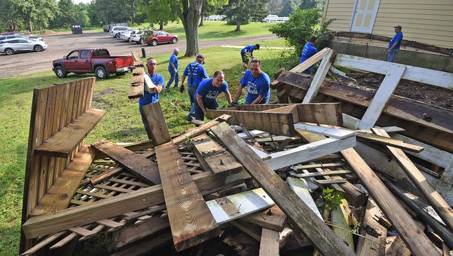 Volunteers scrap a ramp at Raemelton Therapeutic Equestrian Center as part of United Way Day of Caring.