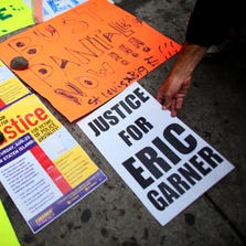 NEW YORK, NY - AUGUST 23: A person adds a banner to the memorial for police violence victim Eric Garner, during a rally against police violence on August 23, 2014 in the Staten Island borough of New York City. Thousands of marchers are expected for today's rally which will be attended by the family of Michael Brown and the Reverend Al Sharpton among others. Eric Garner, 43, died while he was being arrested for allegedly selling loose cigarettes in front of a bodega and was put into a chokehold during a confrontation with police. An investigation is pending and the police officer who allegedly used the illegal chokehold has been placed on modified duty. (Photo by Yana Paskova/Getty Images)