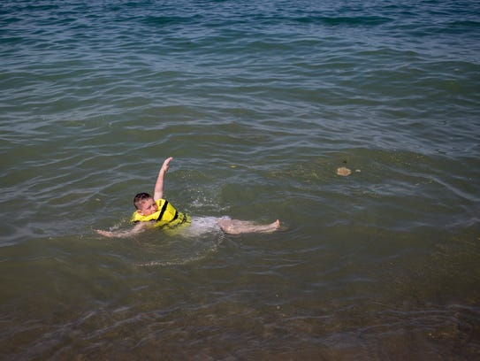 Ernest Cooke Jr., 9, of Lexington, swims with a life