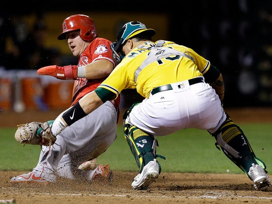 Los Angeles Angels' Mike Trout, left, is tagged out by Oakland Athletics catcher Bruce Maxwell during the fifth inning of a baseball game Tuesday, Sept. 5, 2017, in Oakland, Calif. (AP Photo/Ben Margot)