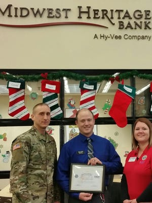 The Iowa Committee for Employer Support of the Guard and Reserve, an agency of the Department of Defense, awarded Corey Lockner of Midwest Heritage Bank, center, with a patriot award in recognition of extraordinary support of an employee serving in the Iowa National Guard and Reserve. He is pictured with Iowa National Guard Lt. Kevin Waldron, left, and Amy Reidel of Iowa's Employer Support of the Guard and Reserve. Waldron nominated Lockner for the award.