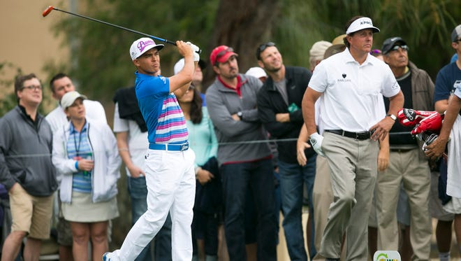 Rickie Fowler hits a tee shot on the second hole of the 2015 Waste Management Phoenix Open as Phil Mickelson looks on TPC Scottsdale.