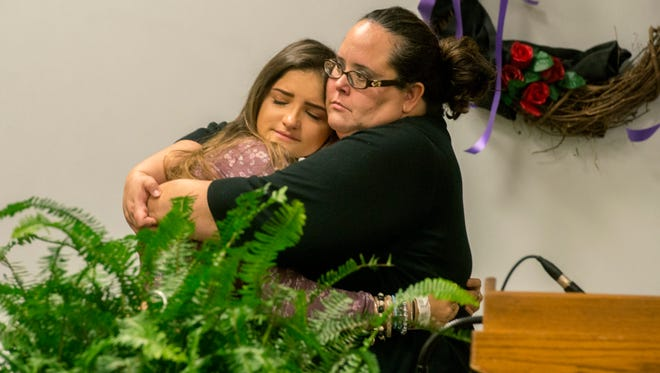 At right, Amy Elliott, the former foster mom of murder victim Amber Robinson, hugs Samantha Gallant, a friend of the teen, during a memorial Sunday at Guy Thompson Community Center in Milton.