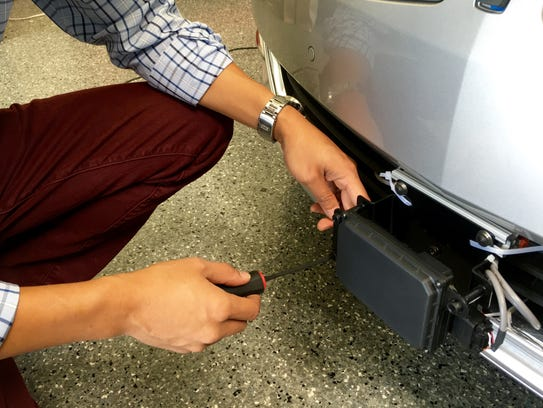 A Drive.ai engineer makes some tweaks to a sensor on