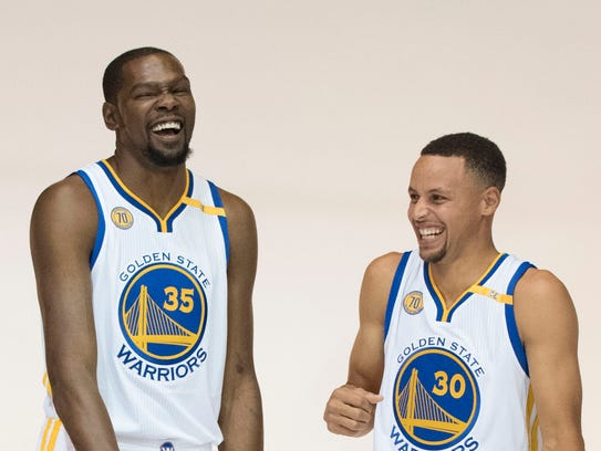 Durant and Stephen Curry laugh during media day at