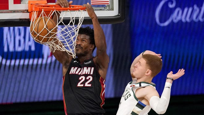 Miami Heat's Jimmy Butler (22) dunks the ball after getting past Milwaukee Bucks' Donte DiVincenzo (0) during the second half Monday in Lake Buena Vista, Fla.