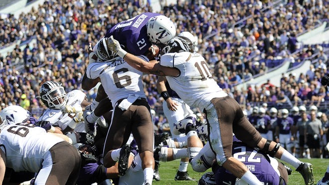 Justin Jackson (21) of the Northwestern Wildcats is tackled by Asantay Brown (6) of the Western Michigan Broncos and Robert Spillane (10) during the first half on September 3, 2016 at Ryan Field in Evanston, Illinois.