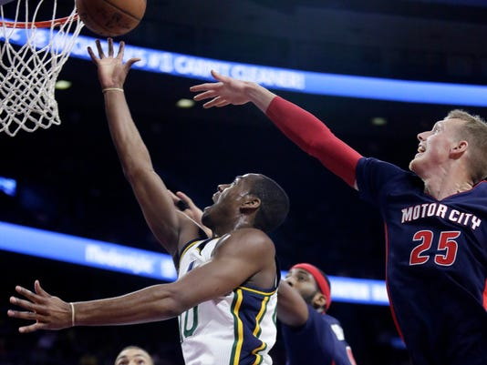 Utah Jazz's Alec Burks goes to the basket past Detroit Pistons' Kyle Singler (25) during the first half of an NBA basketball game Sunday, Nov. 9, 2014, in Auburn Hills, Mich.  (AP Photo/Duane Burleson)