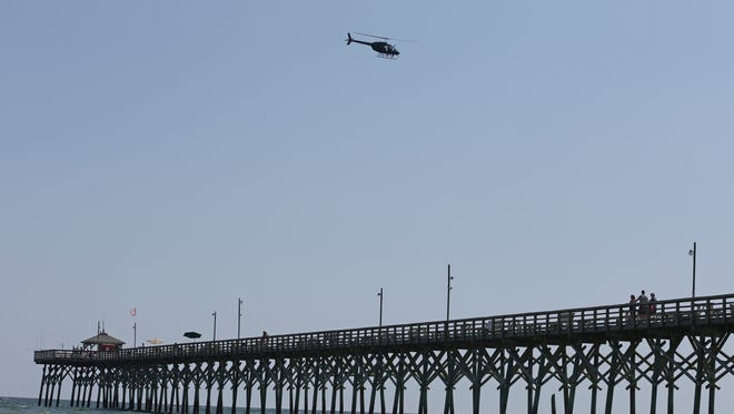 A helicopter flies over the Ocean Crest Pier in Oak Island, N.C.