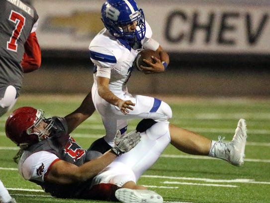 Bowie running back Justin Mendoza is brought down by