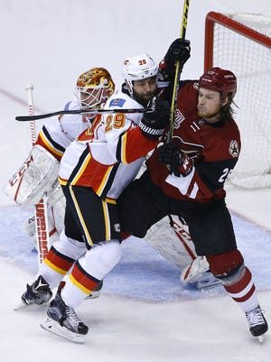 Coyotes' Ryan White (25) and Flames Deryk Engelland (29) fight for a spot in front of goal in the first period at Gila River Arena on December 19, 2016 in Glendale, Ariz.