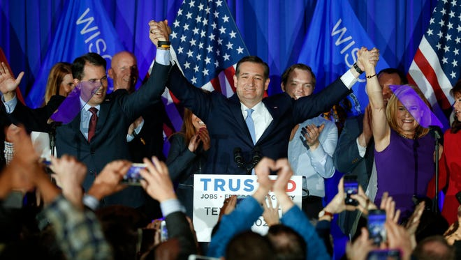 Republican presidential candidate Sen. Ted Cruz, R-Texas, raises hands with Wisconsin Gov. Scott Walker, left, and his wife Heidi, right, during a primary night campaign event, Tuesday, April 5, 2016, in Milwaukee.