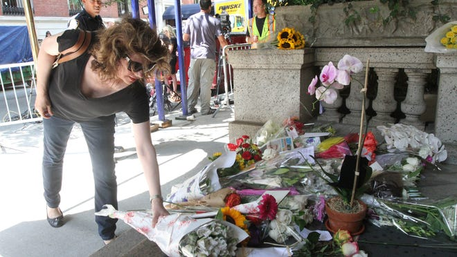 Paula Reardon places flowers at a sidewalk memorial for comedian Joan Rivers at the doorstep of her apartment building, Friday, Sept. 5, 2014 in New York. Rivers died Thursday at a New York hospital following complications from surgery. She was 81.