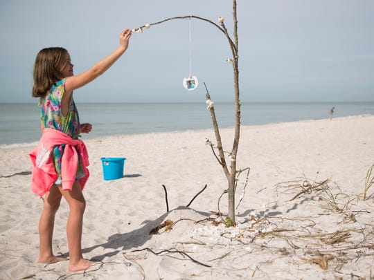 Isabella Murphy, 8, places a shell on a small tree