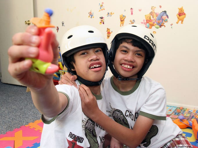 From left, Formerly conjoined twins Carl and Clarence Aguirre play together in the playroom of their Scarsdale home July 31, 2014.