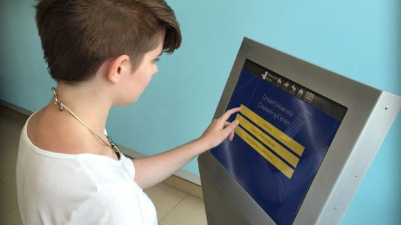 Anna Gibbons, an undergraduate public health major, demonstrates use of the mental health screening kiosk. (Photo courtesy of Drexel University)
