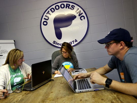 Senior buyer Mary Royer Hays, webmaster Rachelle Cooper and Michael Penn, e-commerce/eBay, discuss sales during a web meeting at the Outdoors Inc. distribution center.