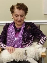 Ollie finds a home in the lap of a nursing home resident.