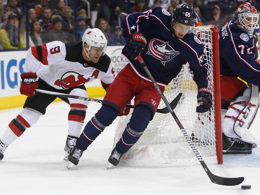 Columbus Blue Jackets' Sergei Bobrovsky, right, of Russia, protects the net as teammate Markus Nutivaara, center, of Finland, carries the puck past New Jersey Devils' Taylor Hall during the first period of an NHL hockey game, Saturday, Feb. 10, 2018, in Columbus, Ohio. (AP Photo/Jay LaPrete)