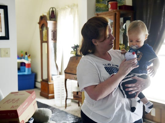 Amy Edwards comforts her 1-year-old grandson while taking a break from cleaning out her Red Lion attic in preparation for her fifth move in 10 years.