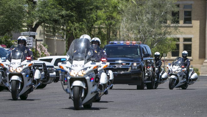 A police motorcade escorts the body of fallen police officer David Glasser to the medical examiner's office in downtown Phoenix.