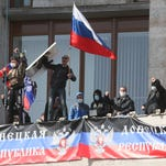 "Pro-Russian activists who seized the main administration building in the eastern Ukrainian city of Donetsk deploy a flag of the so-called Donetsk Republic and hold a Russian flag on April 7, 2014, in Donetsk. They proclaimed on April 7 the creation of a sovereign ""people's republic"" independent of Kiev's rule. Ukraine's embattled Prime Minister on April 7 accused Russia of trying to ""dismember"" his country by plotting seizures of government buildings in eastern regions that are seeking to break away from Kiev."