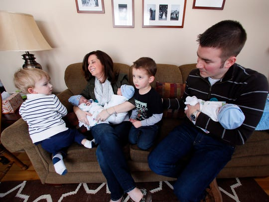 Lauren and Michael Whiteley sit with their boys Nolan, 2, left, Lucas, 3, and identical triplets Alexander, Timothy and Nicholas at their home in St. Clair Shores on Wednesday.