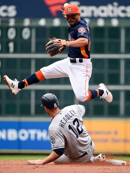 Houston Astros second baseman Jose Altuve, top, drops the ball while attempting a double play over San Diego Padres' Chase Headley during the second inning of a baseball game, Sunday, April 8, 2018, in Houston. Padres' Hunter Renfroe was safe at first. (AP Photo/Eric Christian Smith)