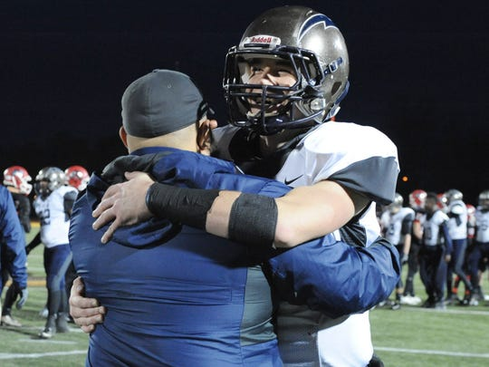 Timber Creek's Devin Leary hugs a coach after a 31-10 victory over Lenape to win the South Jersey Group 4 championship at Rowan University on Sunday. 12.04.16. Joe Warner/For the Courier-Post