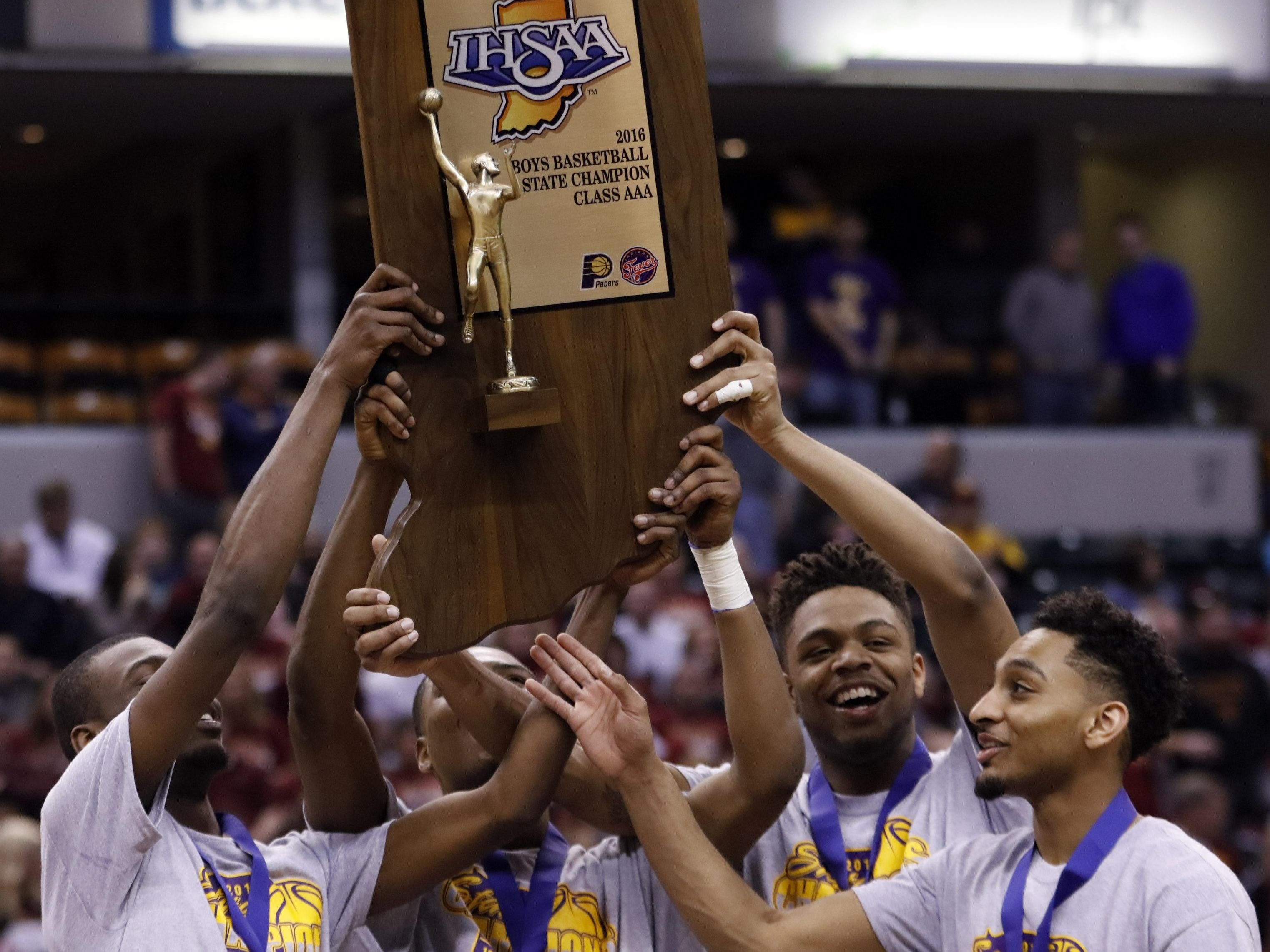 Marion guard Vijay Blackmon, right, and Marion forward Reggie Jones, second from right, hoist the trophy with teammates after defeating Evansville Bosse in the Indiana Class 3A IHSAA state championship basketball game in Indianapolis, Saturday, March 26, 2016. Marion won 73-68. (AP Photo/AJ Mast)