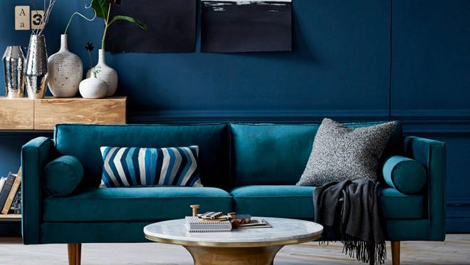 West Elm offers a trim mid-century sofa fall's trendy deep blue. Ceramic vases, nubby throw pillows and a patterned rug add texture.