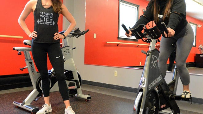 Megan Dunn, owner of Megaphone Fitness in Baltic, left, and instructor Jenny Schlough show on June 9 how their exercise bicycles will be 6 feet apart. Dunn reopened Saturday, three days after the state gave permission for gyms to reopen.