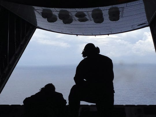 Petty Officer 3rd Class Charles Camarda, left, and Petty Officer 3rd Class Nate Matthews scour the Atlantic Ocean off the coast of Savannah, Ga., Tuesday, July 28, 2015, looking for two missing teenage boaters.