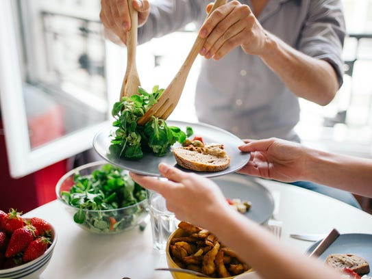 To keep calories in check during holiday dinners, fill half of your plate with fruits and vegetables, which can be eaten first. This provides a sense of fullness as the dinner moves on to other courses, according to health experts.