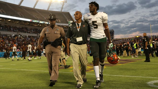 FAMU's Chaviss Murphy puts his arm around Head Coach Alex Wood as they walk off the field against Bethune-Cookman after the Rattlers 29-24 Florida Classic loss at Camping World Stadium in Orlando Saturday, Nov. 18, 2017.