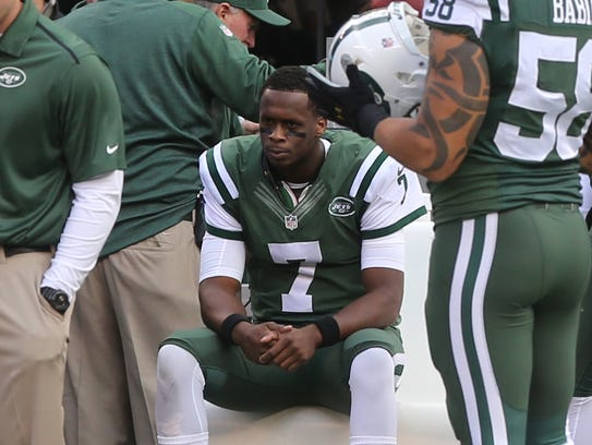 Jets quarterback Geno Smith looks on from the bench