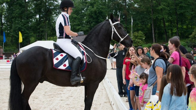 A rider shows her horse off to a crowd of enthusiastic children