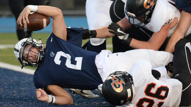 McDowell senior quarterback Chris Juchno, left, crosses the goalline against Cathedral Prep for the first touchdown of the game at Gus Anderson Field on Friday. McDowell won 24-10.