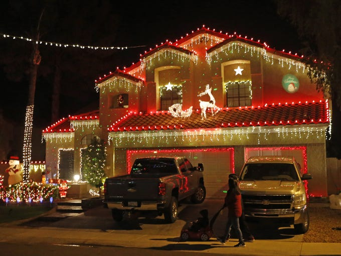 Christmas lights and decorations adorn houses on Upland