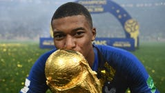 Kylian Mbappe kisses the World Cup trophy after France
