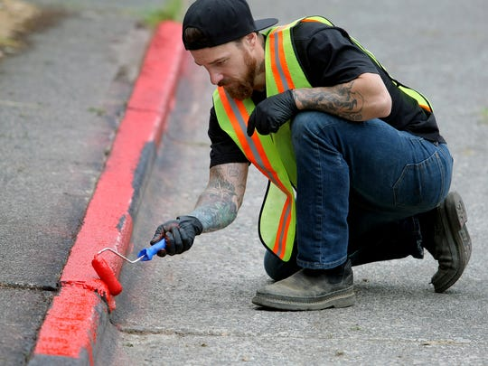 Anthony Wayland paints the curb red on his 15th Street block on Friday. The city now provides red paint to residents in his predicament but the paint is not enforceable by law. He says there's also little to no parking enforcement on his street.