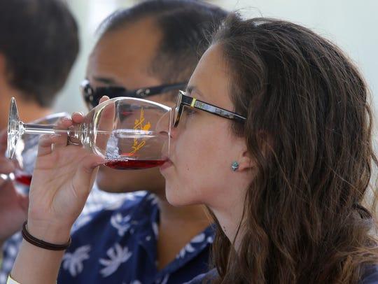 Ashley Avilleira samples wine at the wine tasting tent