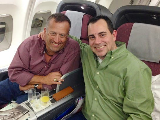 In a March 2014 photo provided by Dale Scott, Major League Baseball umpire Dale Scott, left, sits with his spouse Michael Rausch on a plane going to Australia.  Scott disclosed that he is gay and that he and Raklusch married in November of 2013. (AP Photo/ released by Dale Scott)