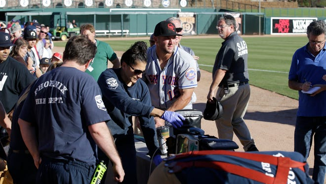 Tim Tebow waits with emergency personnel responding to a fan who passed out following Tebow's debut in the Arizona Fall League.