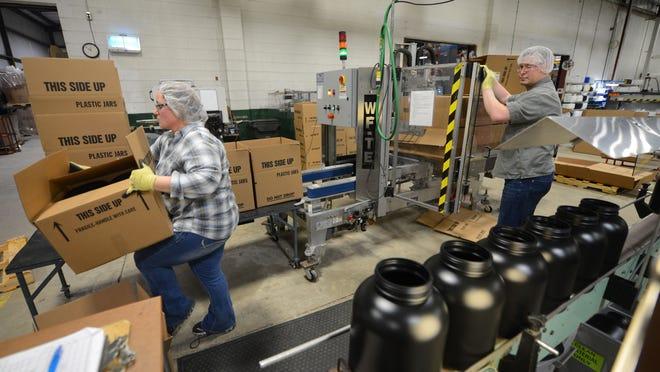 NEW Plastics in Luxemburg worker Amanda Klemik, left, and Steve Mumme load a boxing machine to prepare freshly molded plastic bottles for shipment on Dec. 9.