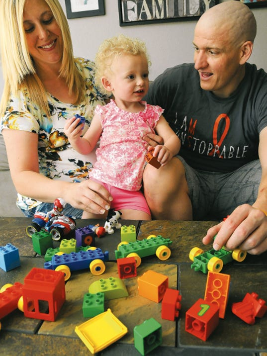 Michael Barrow and his wife Liz play with their daughter Olivia, 2, in the couple's home. Michael Barrow has multiple sclerosis and is participating in a clinical trial for a new treatment.