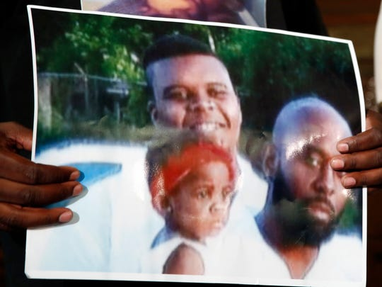 Michael Brown Sr. holds up a photo of himself, right, his son, Michael Brown, top left, and a young child during a news conference in August.