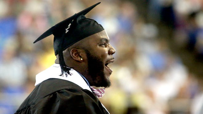 Former MTSU football player Jimmy Staten stands during his graduation ceremony in 2014 after it was announced that he had been drafted by the Seattle Seahawks.